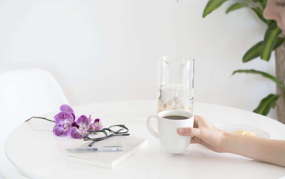 Hand holding coffee with eyeglasses on table