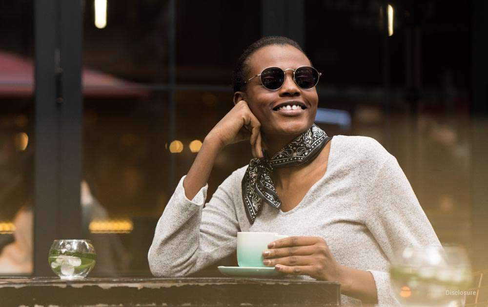 A woman drinking coffee wearing transition glasses
