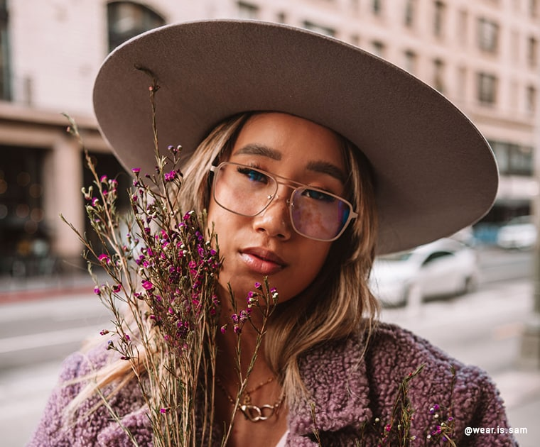 A woman wearing a hat and glasses holding flowers