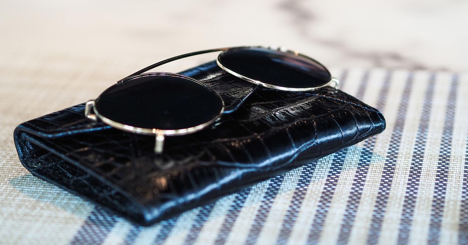 A set of clip-on sunglasses on a black case