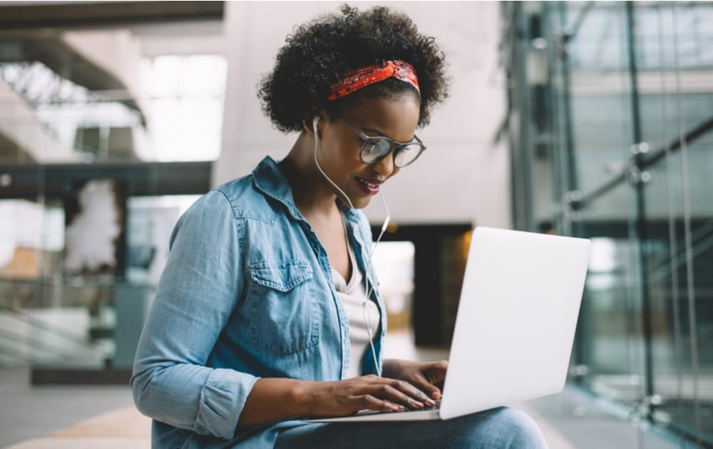 A woman using a laptop wearing blue light blocking glasses
