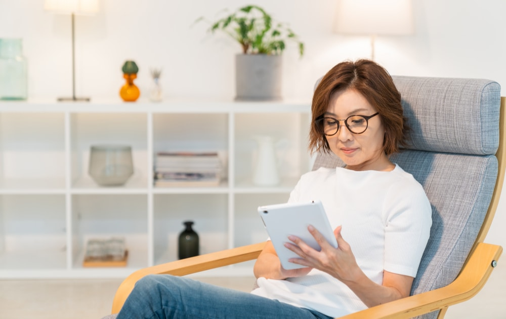 A woman wearing glasses sitting down and using a tablet