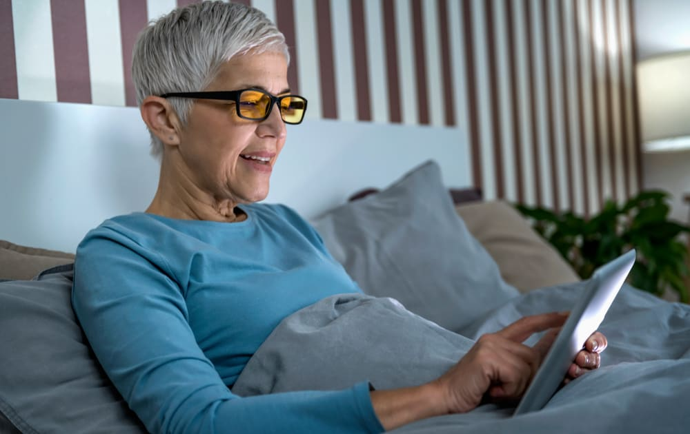 A women in bed using a tablet wearing blue light blocking glasses