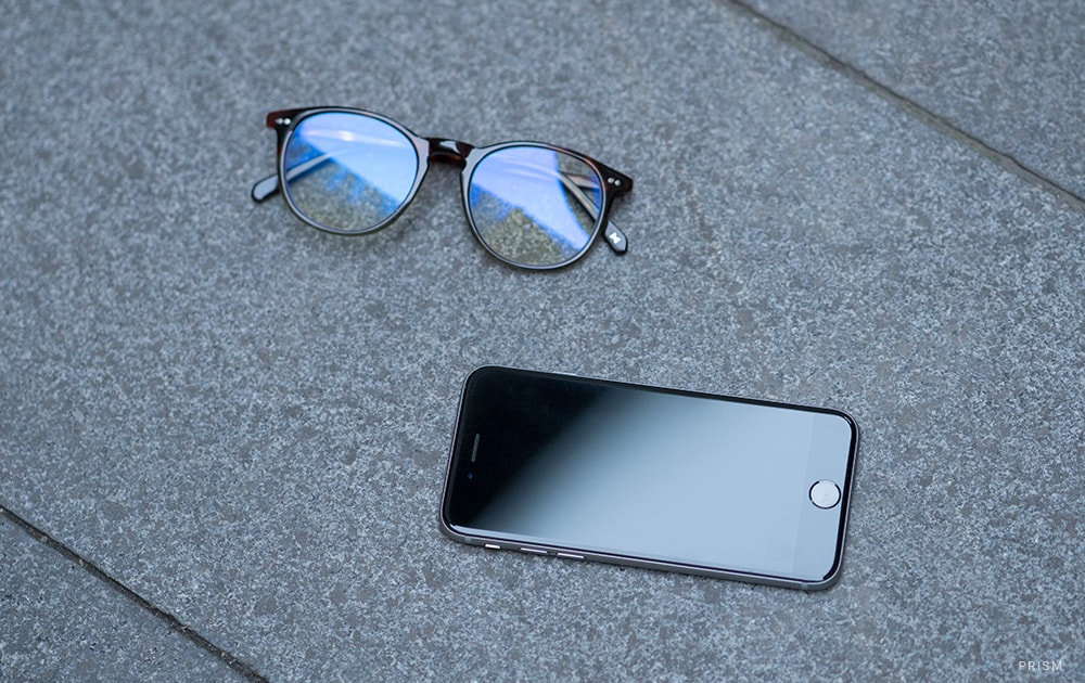 A pair of blue light blocking glasses next to a smartphone