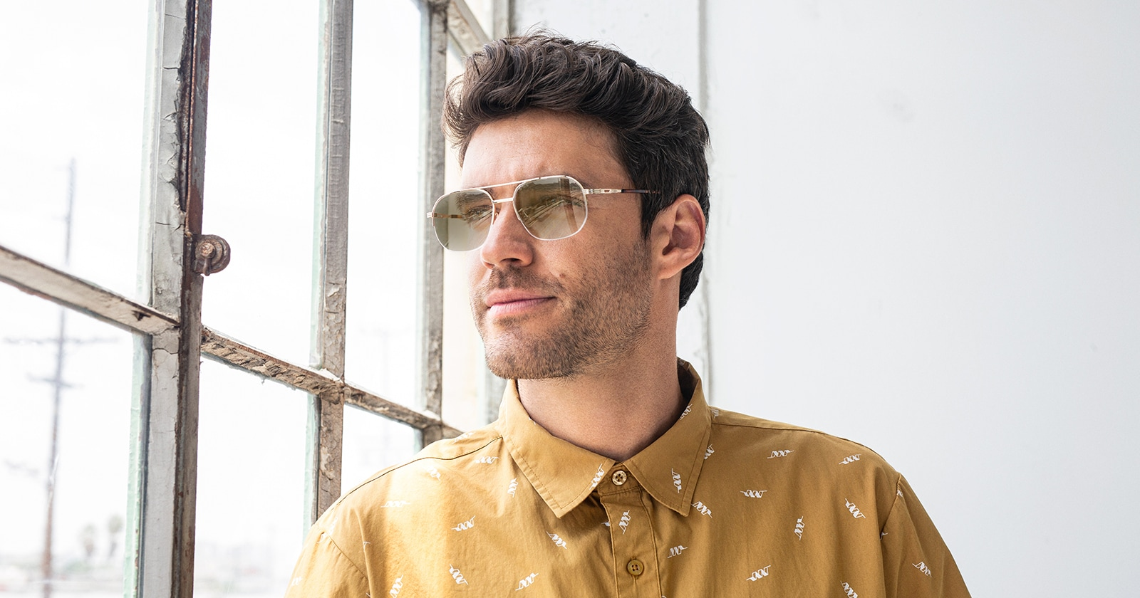 A man in front of a window wearing transition glasses