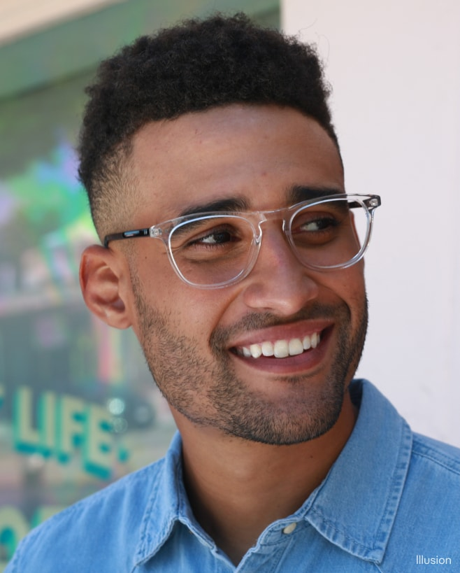 A smiling man wearing clear-frame eyeglasses