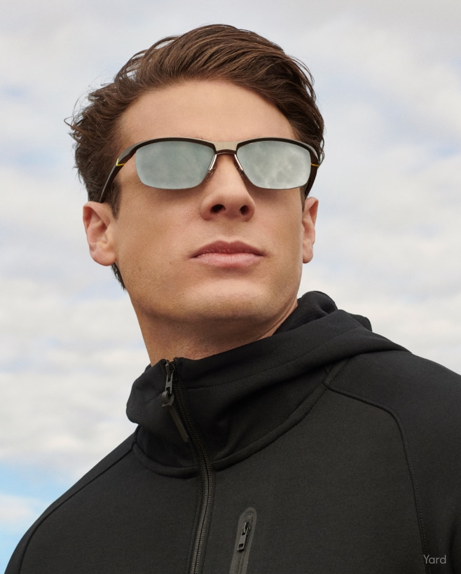 A man in a black jacket wearing mirrored sunglasses