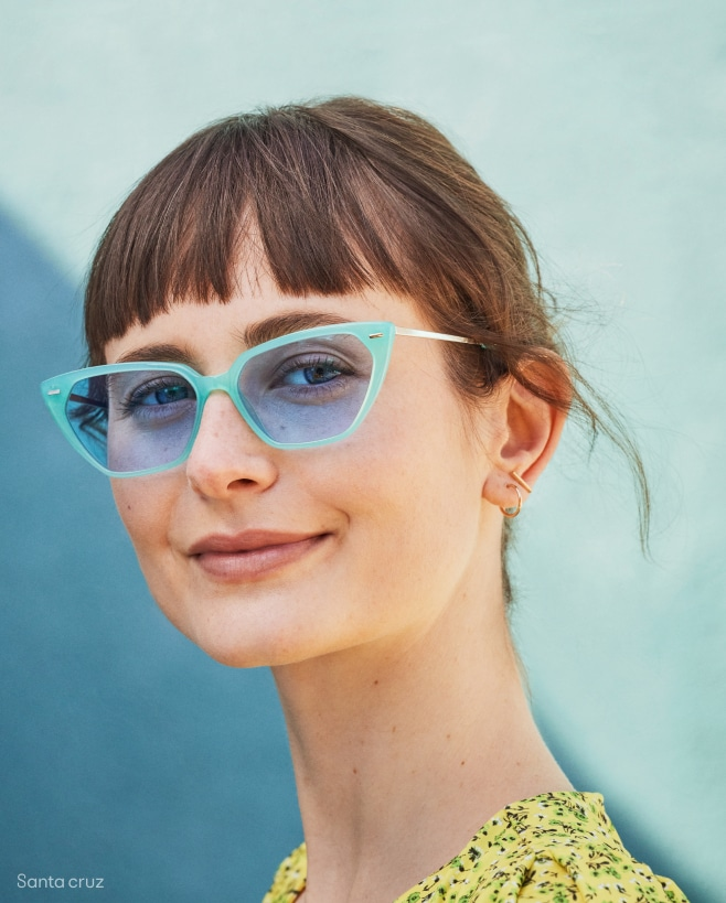 A woman wearing blue cat-eye sunglasses with eyeliner