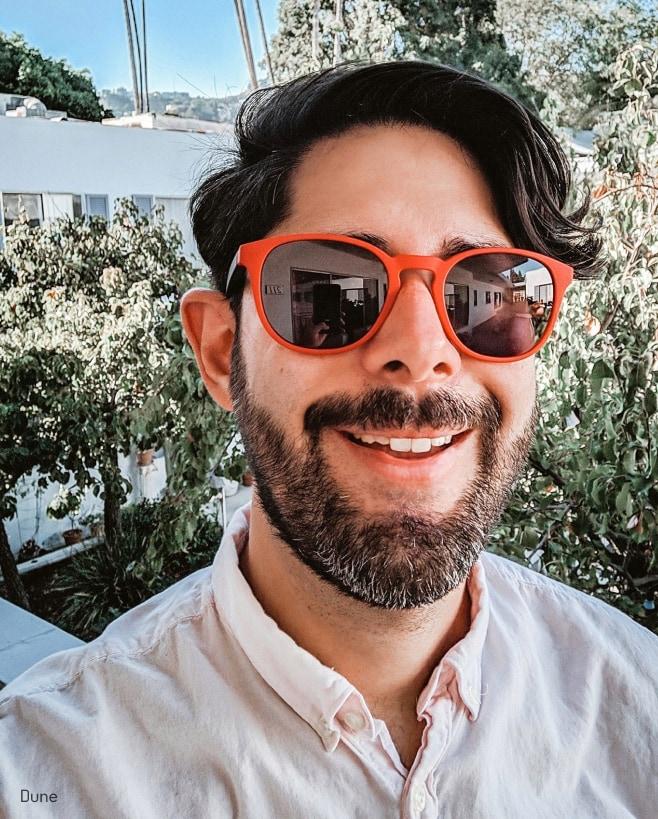 A man smiling wearing crimson eyeglasses