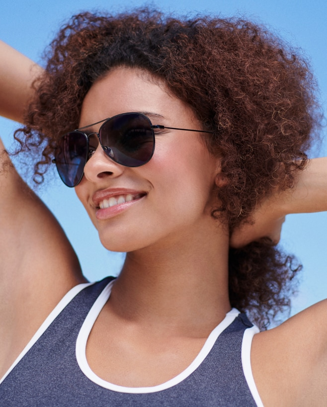 A woman with curly brown hair wearing aviator sunglasses