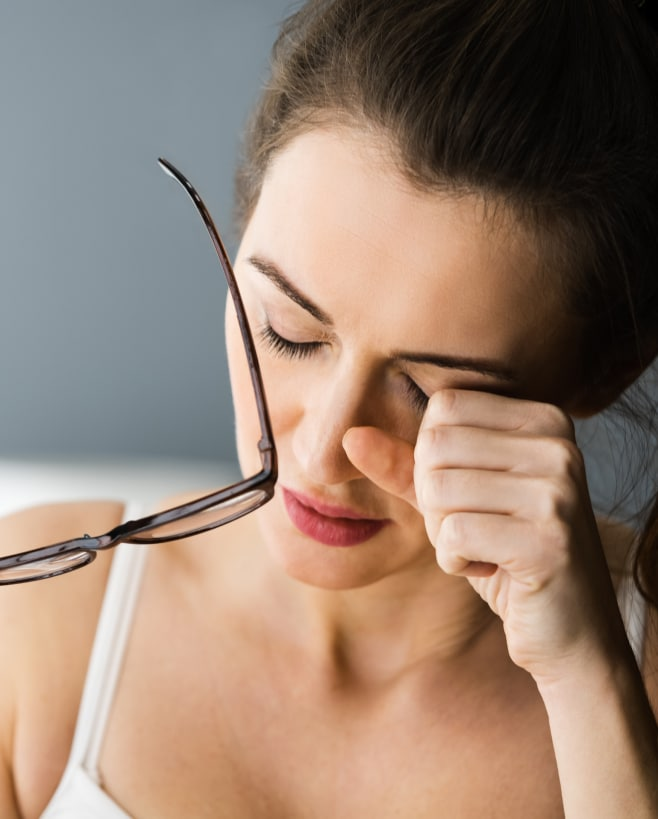 A woman rubbing her eyes due to eye strain